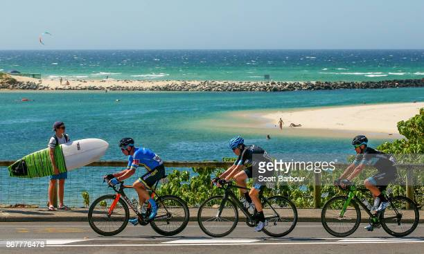 A boy with a surfboard watches as cyclists compete during the Road Race Test Event on October 29 2017 in the Gold Coast Australia The Road Race is a...