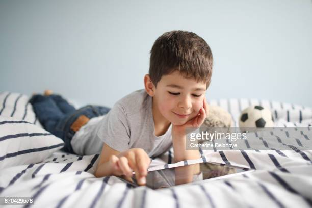 a boy with a tablet on his bed - tablette numérique stock pictures, royalty-free photos & images