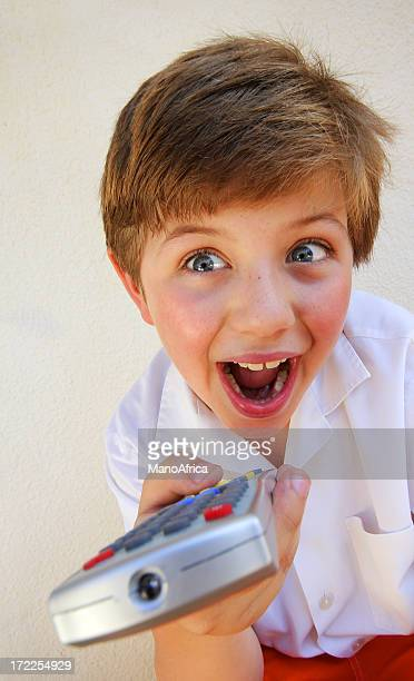 boy with a television remote - infrared lamp stock photos and pictures