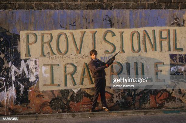 A boy with a toy gun stands in front of a Provisional IRA mural in the heart of the Catholic and Republican community of west Belfast 15th September...