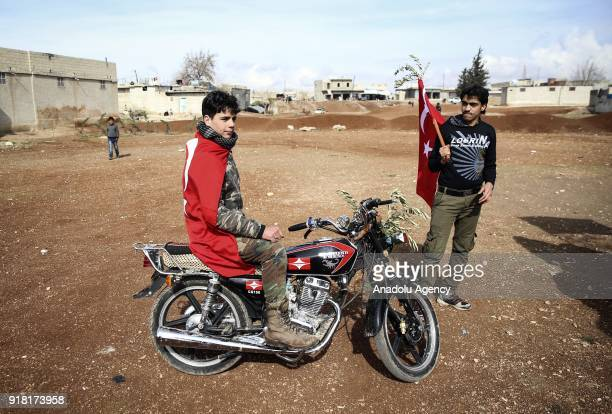 A boy with a Turkish flag and an olive branch is seen on a motorcycle as part of a convoy in support of 'Operation Olive Branch' launched in Syria's...