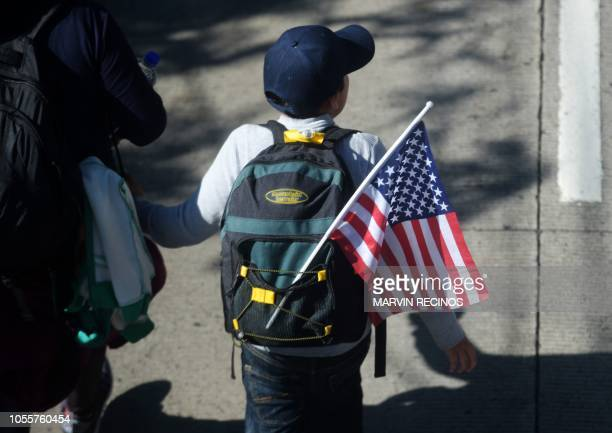 A boy with a US flag joins Salvadoran migrants embarking on a journey in caravan to the United States in San Salvador on October 31 2018 Many...