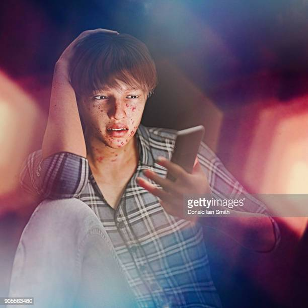 boy with acne texting on cell phone - cyberbullying stock photos and pictures