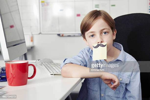 boy with adhesive note covering mouth, drawing of moustache - role reversal stock photos and pictures