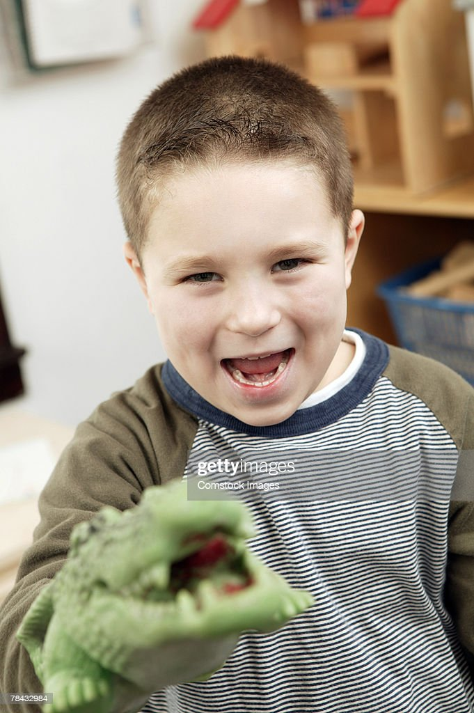Boy with alligator puppet : Stockfoto