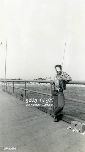 A boy with an eye patch poses with his fishing pole on the pier in Manhattan Beach California circa 1940