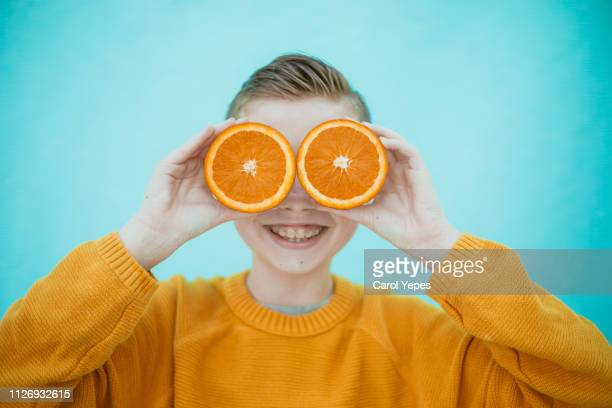 boy with an orange  in front of  eyes - one boy only stock pictures, royalty-free photos & images