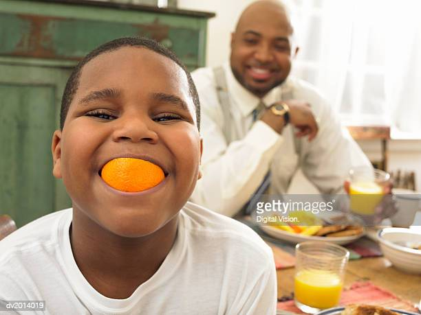 Boy With an Orange in His Mouth at Breakfast and His Father in the Background