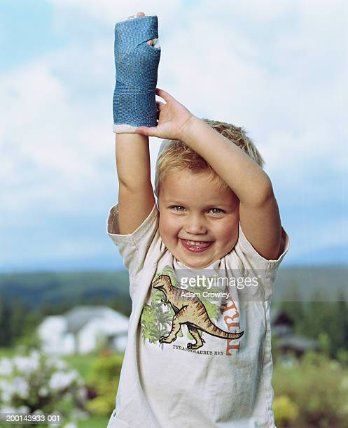 Boy (3-5) with arm in cast, arm raised, portrait