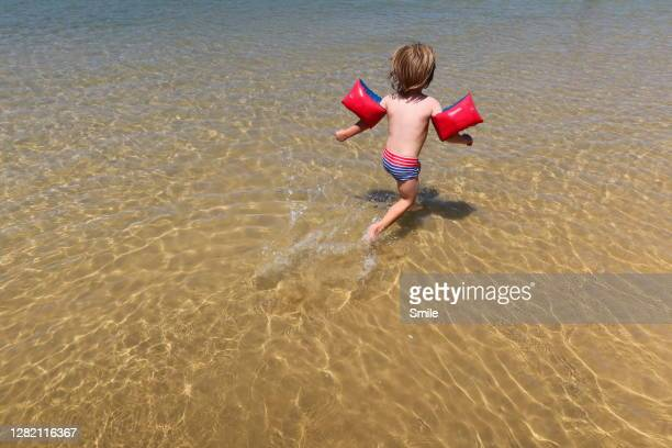 boy with armbands running across the water - arm band stock pictures, royalty-free photos & images