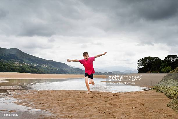 Boy with arms outstretched running on beach