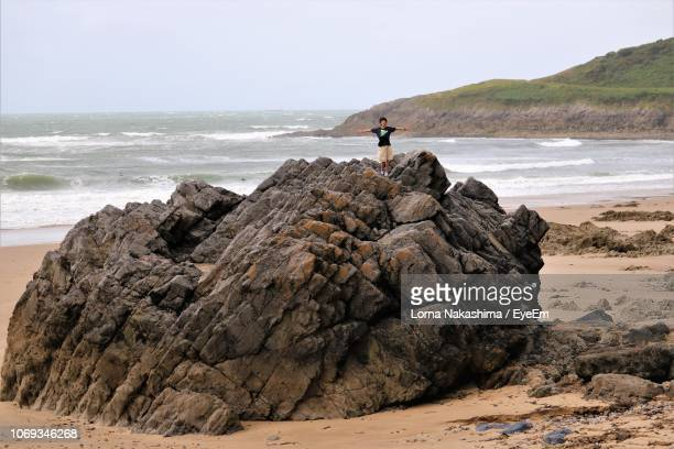 Boy With Arms Outstretched Standing On Rock Formation By Sea Against Sky