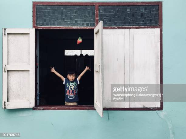 Boy With Arms Raised Seen Through Window