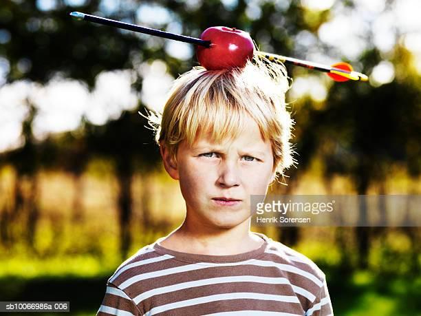 Boy (4-5) with arrow through apple