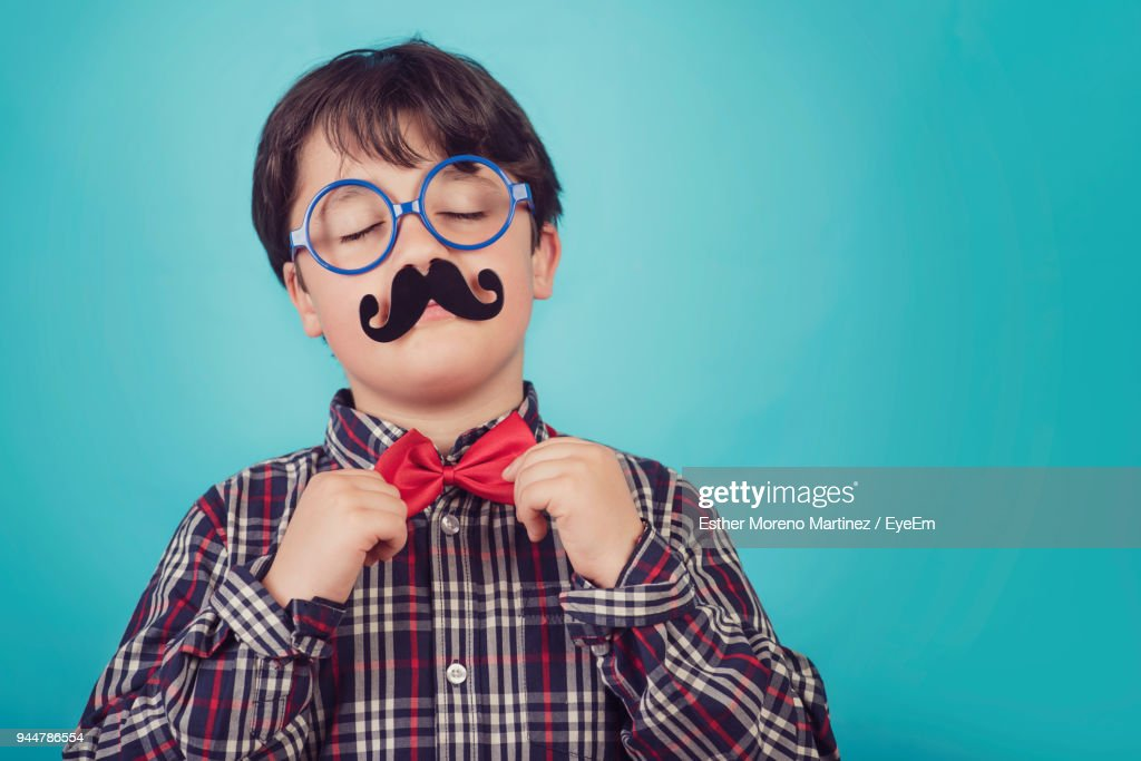 Boy With Artificial Mustache Against Blue Background : Stock Photo