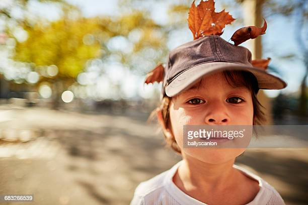 Boy With Autumn Leaves In Hat.