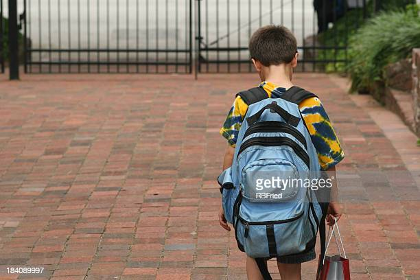 Boy with backpack holding bag walking toward closed hate