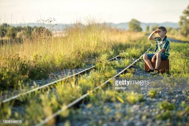 junge mit sack balancieren auf gleisen - kemter stock-fotos und bilder