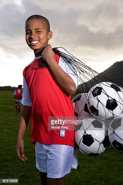 Boy with bag of footballs