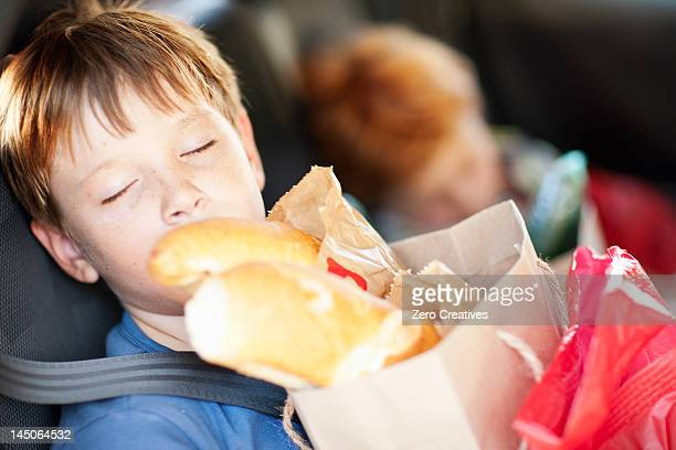 boy with bag sleeping in backseat - family inside car stock photos and pictures