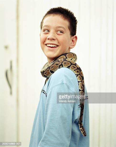 Boy (11-13) with Ball python (Python regius) around neck