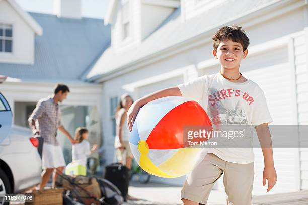Boy with beach ball in driveway