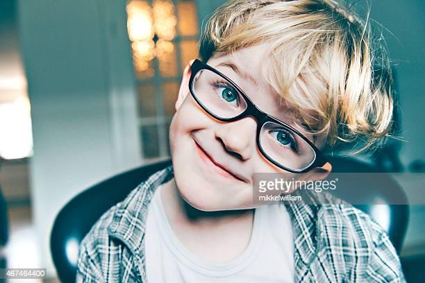 Petit garçon avec grosse noir lunettes fait une drôle de sourire