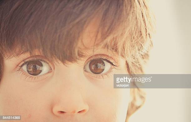 Boy (2-3) with big eyes staring at camera