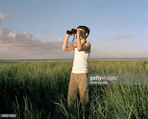 Boy with binoculars in high grass