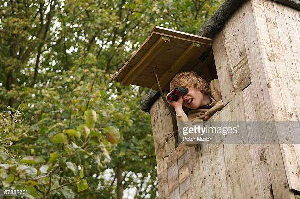 Boy with binoculars in treehouse