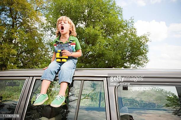 Niño con binoculares, ubicado en el último piso de automóviles