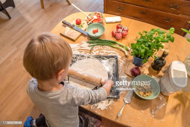boy with blond hair rolling pizza dough at home - vegetarian pizza stock pictures, royalty-free photos & images