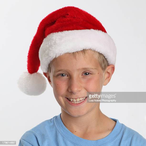 boy with blue eyes wearing santa hat - santa hat stock photos and pictures