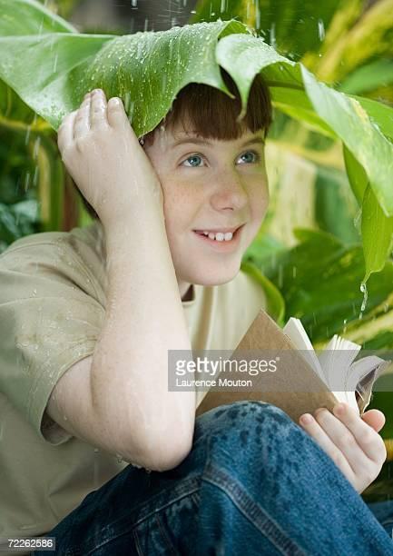 Boy with book sitting under leaf in rain