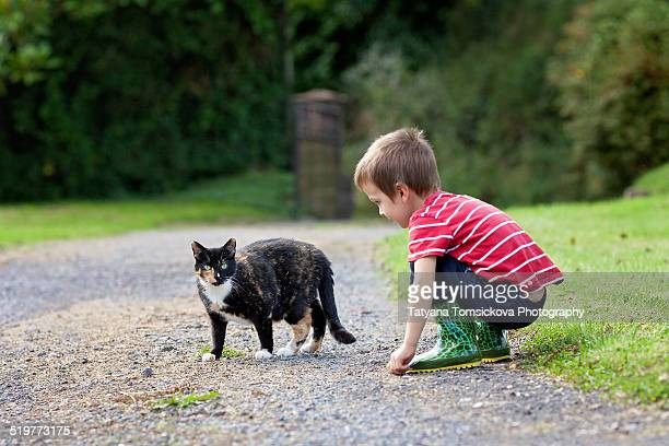 Boy with boots, looking at a cute cat