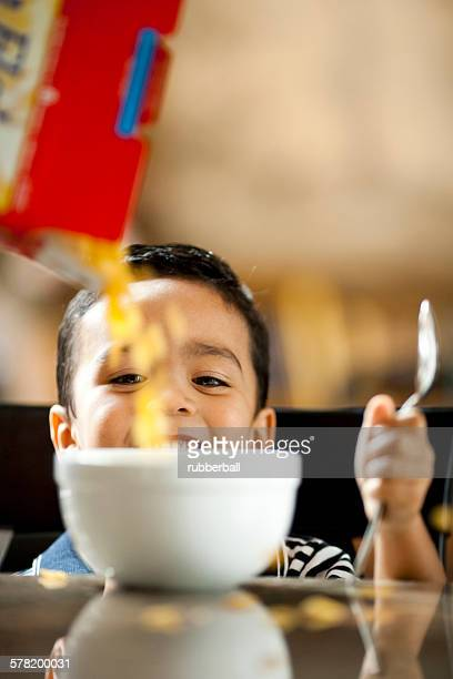 Boy with bowl of cereal and spoon smiling