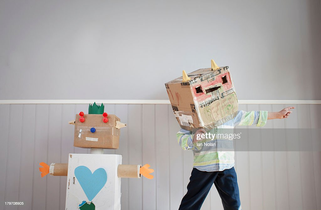 Boy with box covering head and homemade toy robot : Stock Photo