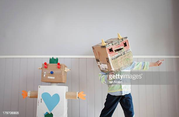 boy with box covering head and homemade toy robot - vorstellungskraft stock-fotos und bilder