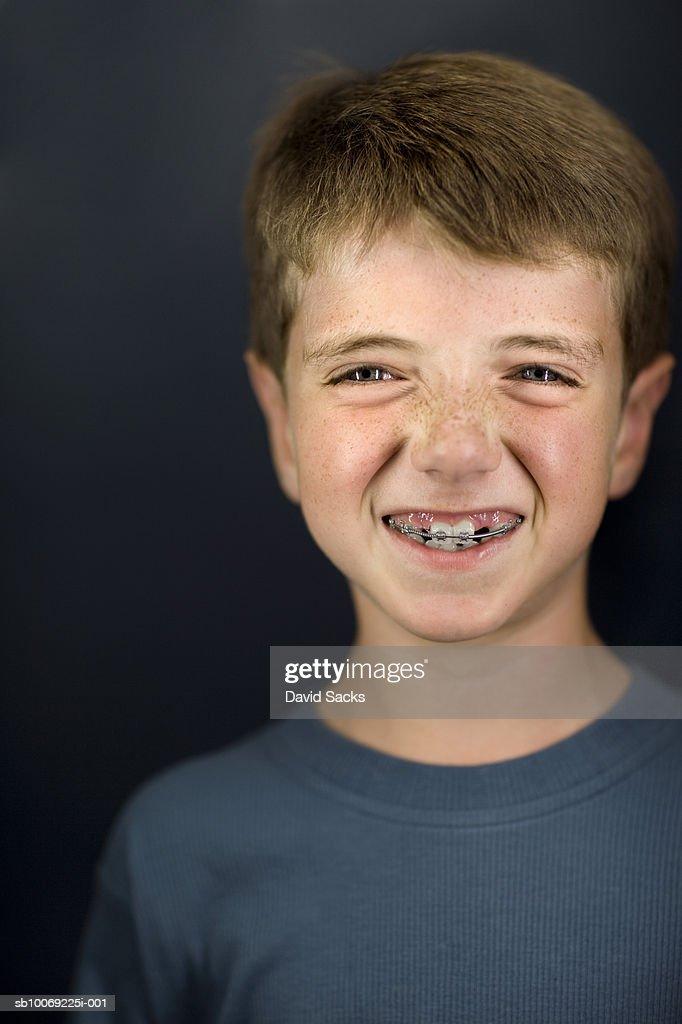 Boy (6-7) with brace, smiling, close-up, portrait : Stockfoto