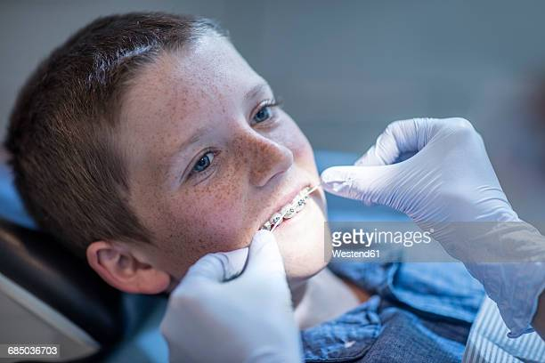 Boy with braces in dental surgery receiving dental floss treatment