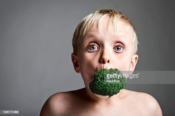 Junge mit Brokkoli gefüllte in den Mund
