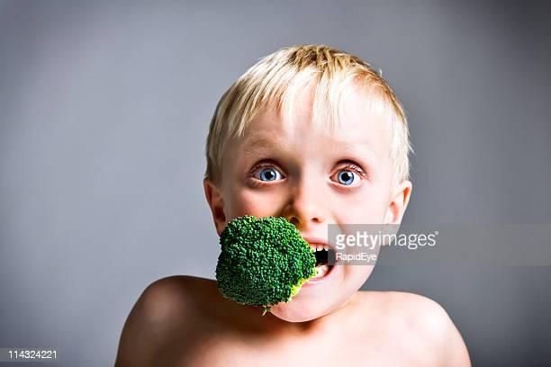 Niño con brécol relleno en la boca