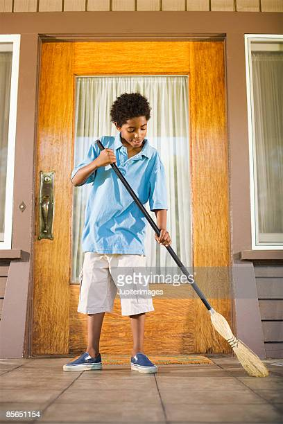 Boy with broom sweeping porch