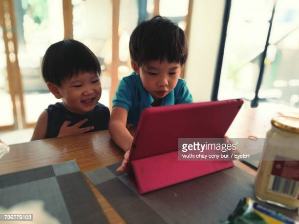 Boy With Brother Using Digital Tablet At Table