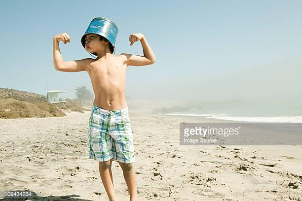 Boy with bucket on head, flexing muscles