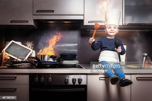 Boy with burning chef's hat in burning kitchen