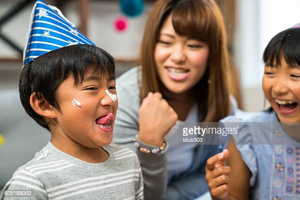 Boy with cake on his face at a family celebration
