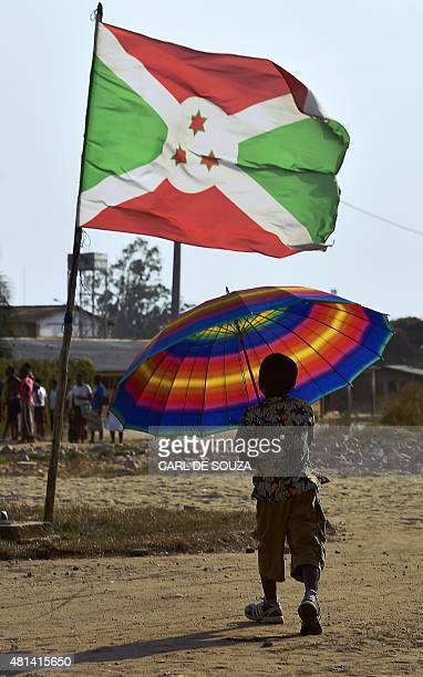 Boy with carries an umbrella near a Burundian flag in Bujumbura on July 20, 2015. The small, landlocked African country of Burundi holds...