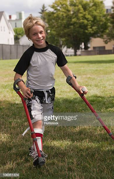 boy with cerebral palsy walking with the support of crutches - paralisia cerebral - fotografias e filmes do acervo