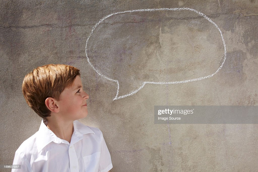 Boy with chalk speech bubble on wall : Stock Photo